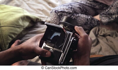 Man takes photo of the woman on old moving-film photocamera...
