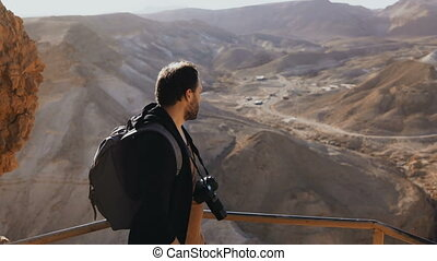 Man takes photos of amazing desert landscape. European male...
