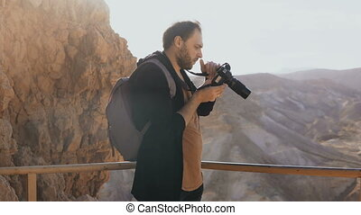 Man takes photos of massive mountain scenery. Caucasian male...