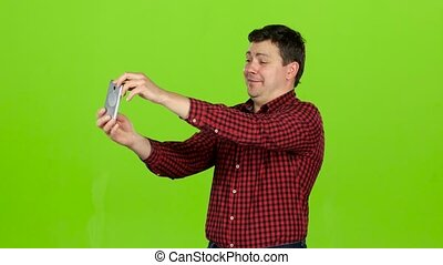 Man takes pictures on the phone, he is happy and cheerful. Green screen