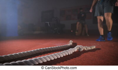 Man takes rope in his hands and prepares to do workout.