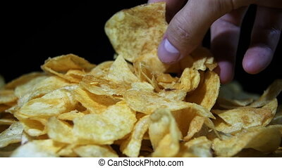 Man Takes the Potato Chips by hand on a Wooden Table on...