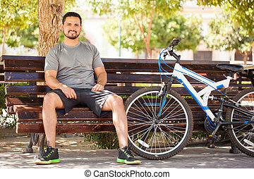 Man taking a break from exercising on his bicycle - Full...