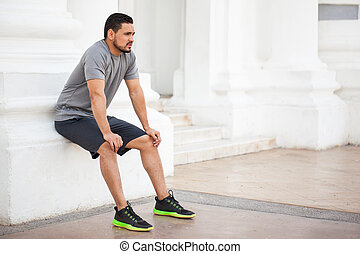 Man taking a break from exercising outdoors