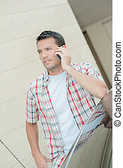 Man taking a call next to his car