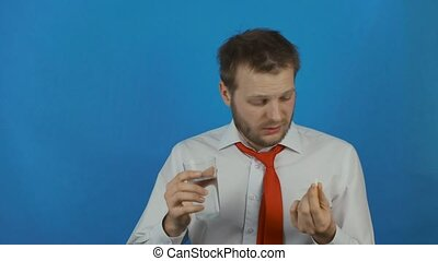 man taking a headache pill due to hangover after alcohol party or hard day's work