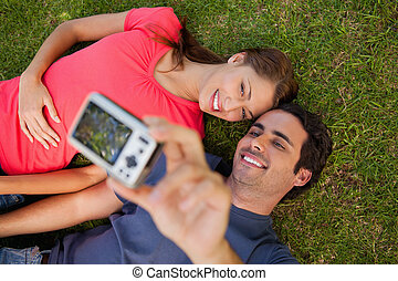 Man taking a photo with his friend while lying side by side