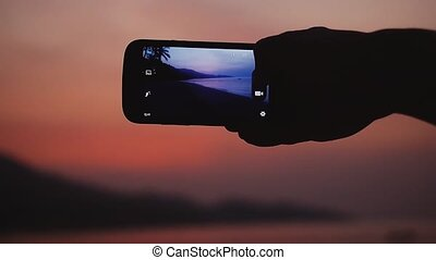 Man taking a picture of beautiful evening sky on mobile phone. Slow motion. 1920x1080