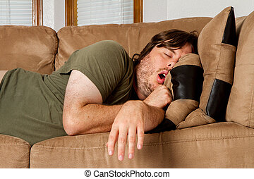 He is asleep mouth open and arm just flung over the side of the couch.