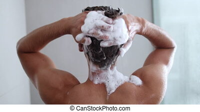 Man taking a shower washing hair with shampoo product under ...