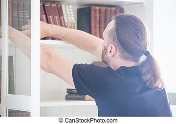 Man taking book from shelf - people, knowledge, education ...