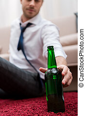 Man taking bottle of beer while sitting on a carpet in the living room