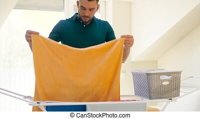 man taking laundry from drying rack at home - laundry and...