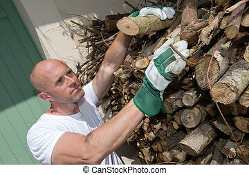 Man taking logs from stack