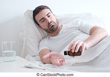 Man taking medicine pills lying in the bed
