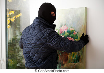 Man taking off painting - A masked man trying to take a...