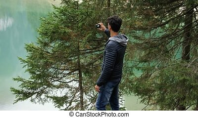 Man taking photo at lake with action cam - Young handsome...