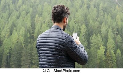 Man taking photo at lake with smartphone