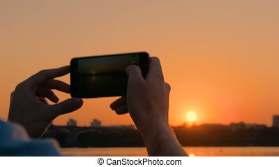 Man taking photo of sunset with smartphone on city quay -...