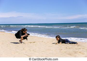 Man taking photo of teenage boy on sandy beach