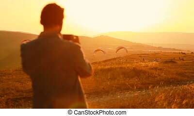Man taking photo of the rising paragliders in mountains