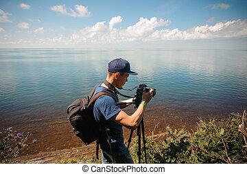 man taking photo, photographing lake