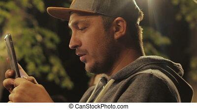 Man taking photo with camera phone at night