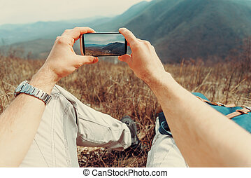 Man taking photographs mountain with smartphone - Hiker man...