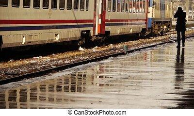 Man taking photographs of trains - Man walking along...