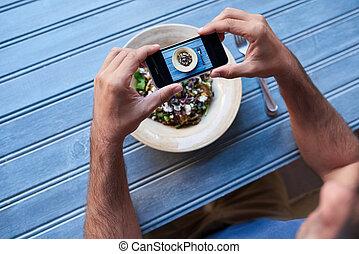 Man taking photos of his salad at a blue table - Man sitting...