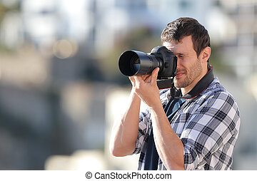 Man taking photos with a dslr camera in a town