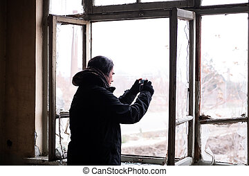 Man taking photos with his mobile inside of an abondened ...