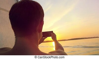 Man taking picture from his mobile phone of amazing sunset over sea while traveling on yacht in slowmotion.