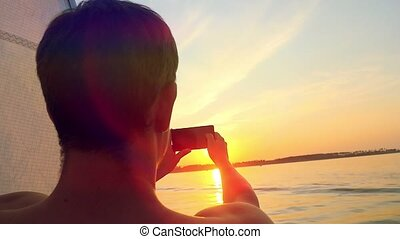 Man taking picture from his mobile phone of beautiful sunset over sea while traveling on yacht in slowmotion.
