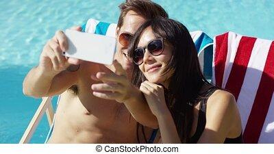 Man taking picture of himself with wife at pool