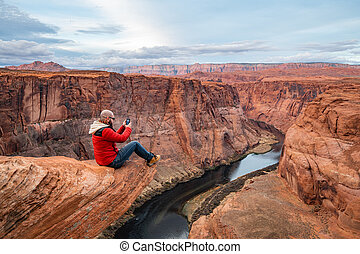Man taking picture with mobile phone while sitting on a cliff over Colorado river in Horseshoe bend canyon