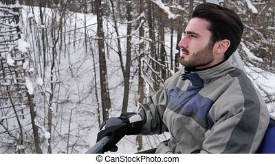 Man taking ride on chairlift while skiing - Portrait of...