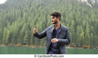 Man taking selfie at lake