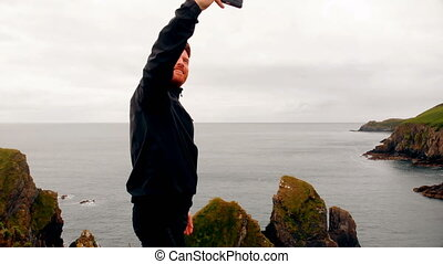 Man taking selfie from mobile phone on cliff 4k - Young man ...