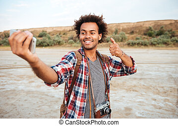 Man taking selfie with mobile phone and showing thumbs up