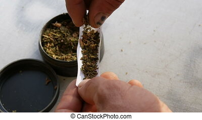 A man taking thin paper and shredded tobacco out of a plastic bag and rolling himself a cigarette on a white background close up view