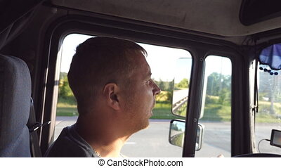 Man talking and driving truck through countryside on a warm summer day. Profile of truck driver. Trucker riding at the car. Side view Close up Slow motion