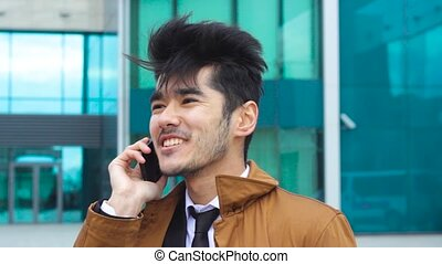 Man talking by phone in windy day in front of business...