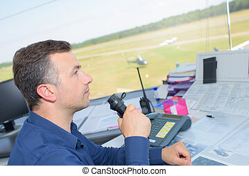 Man talking into control tower receiver