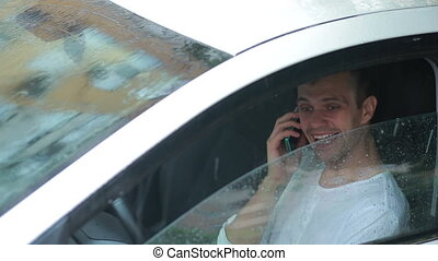 man talking on a cell phone while sitting in the car. smiling driver
