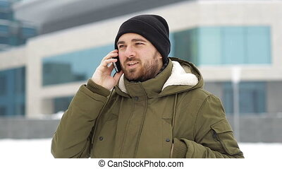 Man talking on a mobile cell phone in winter outdors
