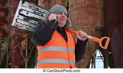 Man talking on cell phone near tank