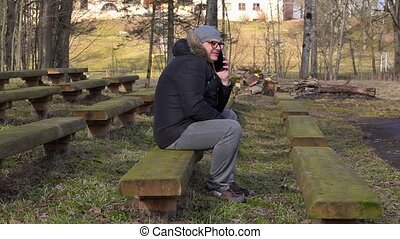 Man talking on cell phone on bench