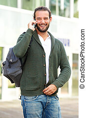 Man talking on cell phone with backpack outside