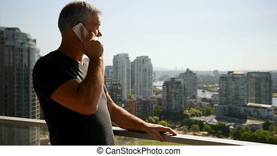 Man talking on mobile phone in balcony 4k - Man talking on...